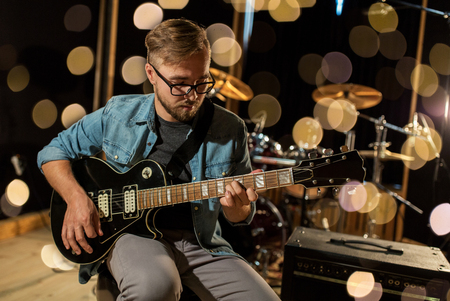 Photo for music, people, musical instruments and entertainment concept - male guitarist playing electric guitar at studio rehearsal over lights - Royalty Free Image