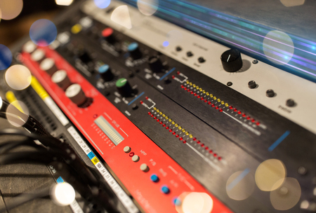Photo for music, technology, electronics and equipment concept - close up of mixing console at sound recording studio over lights - Royalty Free Image