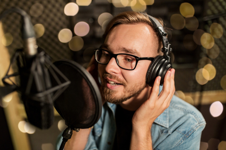 Photo for man with headphones singing at recording studio - Royalty Free Image