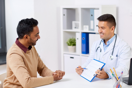 Photo pour happy doctor and male patient meeting at hospital - image libre de droit