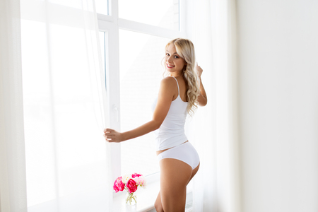 Photo pour woman in underwear at window in morning - image libre de droit