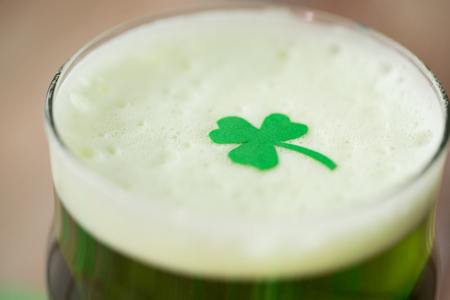 Photo pour close up of glass of green beer with shamrock - image libre de droit