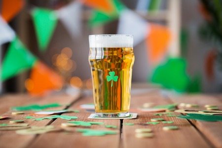 Foto de glass of beer, shamrock and coins on wooden table - Imagen libre de derechos