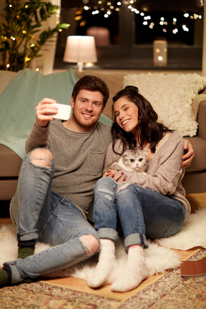 Photo pour happy couple taking selfie by smartphone at home - image libre de droit