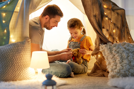 Foto de happy family playing with toy in kids tent at home - Imagen libre de derechos