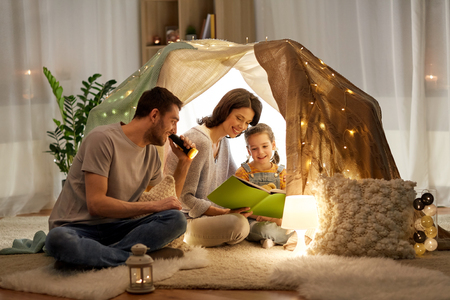 Foto de happy family reading book in kids tent at home - Imagen libre de derechos