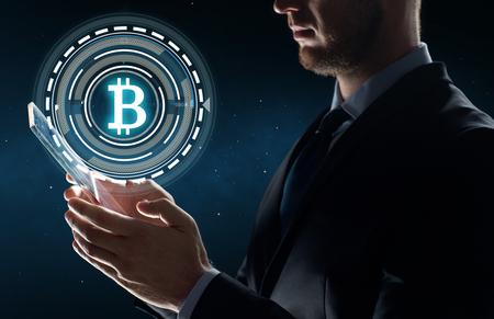 Photo pour businessman with tablet pc and bitcoin hologram - image libre de droit