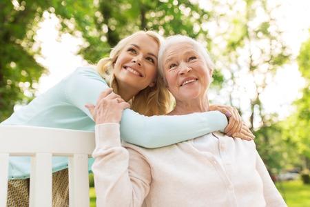 Foto de daughter with senior mother hugging on park bench - Imagen libre de derechos
