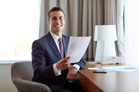Photo pour businessman with papers working at hotel room - image libre de droit