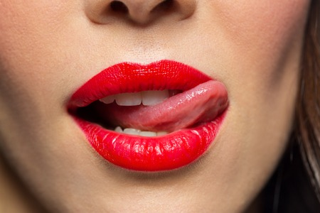 Foto de close up of woman with red lipstick licking lips - Imagen libre de derechos
