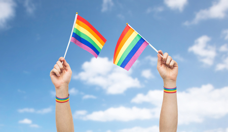 Foto de hand with gay pride rainbow flags and wristbands - Imagen libre de derechos