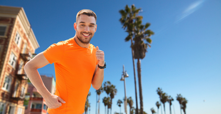 Foto de smiling young man running at summer seaside - Imagen libre de derechos