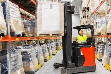 Foto de loader operating forklift at warehouse - Imagen libre de derechos