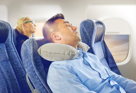Foto de man sleeping in plane with cervical neck pillow - Imagen libre de derechos