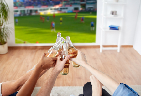 Photo pour friends clinking beer and watching soccer game - image libre de droit