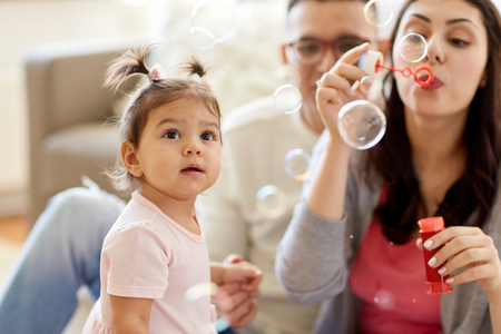 Foto de family with soap bubbles playing at home - Imagen libre de derechos