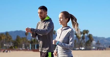 Foto de couple with fitness trackers running outdoors - Imagen libre de derechos