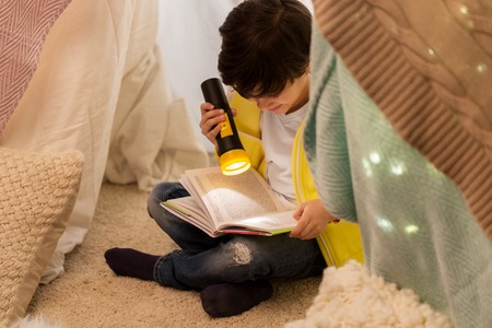 Foto de happy boy reading book in kids tent at home - Imagen libre de derechos