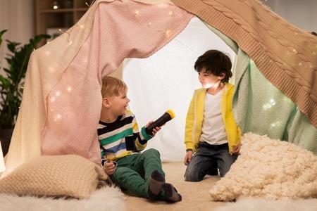 Foto de happy boys with torch light in kids tent at home - Imagen libre de derechos