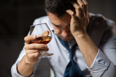 Foto de alcoholism, alcohol addiction and people concept - close up of male alcoholic drinking brandy at night - Imagen libre de derechos