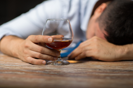 Photo pour alcoholism, alcohol addiction and people concept - male alcoholic with glass of brandy lying or sleeping on table at night - image libre de droit