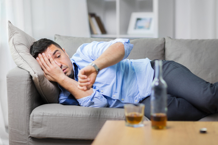 Foto de alcoholic lying on sofa and looking at wristwatch - Imagen libre de derechos