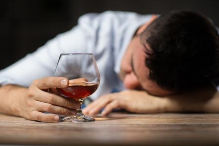 Foto de drunk man with glass of alcohol on table at night - Imagen libre de derechos
