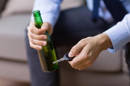 Photo pour male driver hands holding beer bottle and car key - image libre de droit