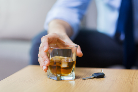 Photo for close up of hand with alcohol and car key on table - Royalty Free Image