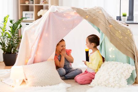 Foto de little girls with torch light in kids tent at home - Imagen libre de derechos