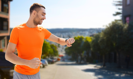 Foto de sport, technology and healthy lifestyle concept - smiling young man with smart watch or fitness tracker over san francisco city background - Imagen libre de derechos