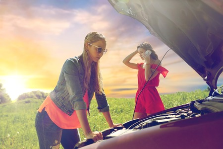 Foto de women with open hood of broken car at countryside - Imagen libre de derechos