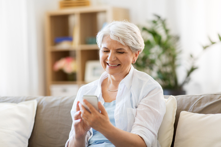 Foto de happy senior woman with smartphone at home - Imagen libre de derechos