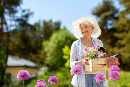 Photo pour senior woman garden tools and flowers at summer - image libre de droit