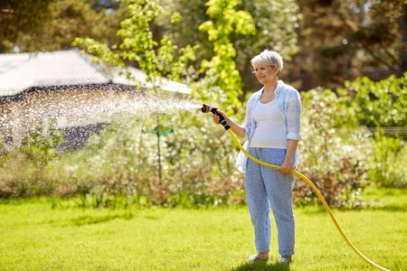 Foto de senior woman watering lawn by hose at garden - Imagen libre de derechos