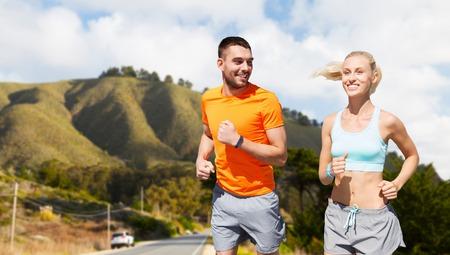 Foto de smiling couple running over big sur hills - Imagen libre de derechos
