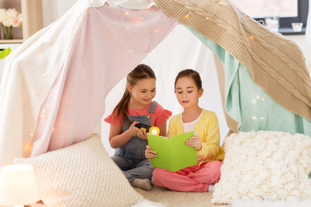 Foto de little girls reading book in kids tent at home - Imagen libre de derechos
