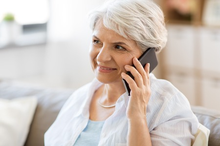 Foto de senior woman calling on smartphone at home - Imagen libre de derechos