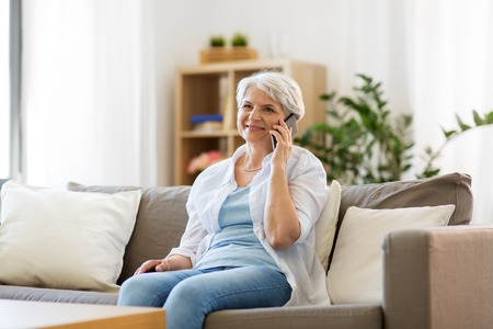 Photo pour senior woman calling on smartphone at home - image libre de droit