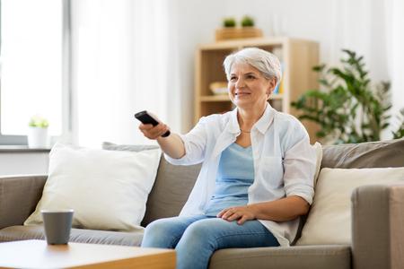 Foto de senior woman with remote watching tv at home - Imagen libre de derechos