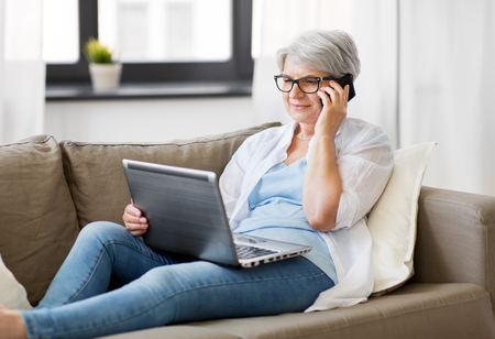 Foto de technology, old age and people concept - happy senior woman in glasses with laptop computer calling on smartphone at home - Imagen libre de derechos