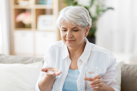 Foto de age, medicine, healthcare and people concept - senior woman with glass of water taking pills at home - Imagen libre de derechos