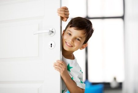 Photo for childhood, fun and people concept - happy little boy behind door at home - Royalty Free Image