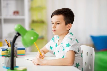 Photo pour little boy writing to notebook at home - image libre de droit