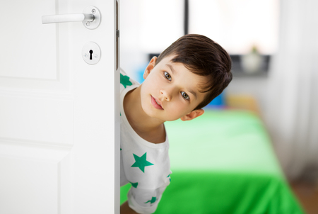 Photo for little boy behind door at home - Royalty Free Image