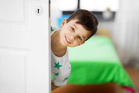 Photo for happy little boy behind door at home - Royalty Free Image
