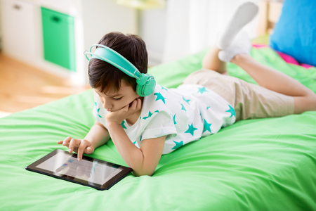 Photo pour boy with tablet pc and headphones at home - image libre de droit