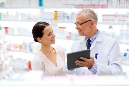 Foto de apothecary and customer with tablet pc at pharmacy - Imagen libre de derechos