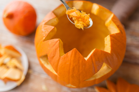 Photo pour halloween, decoration and holidays concept - close up of spoon carving pumpkin flesh and making jack-o-lantern at home - image libre de droit