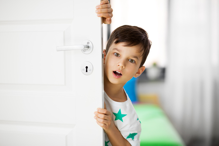 Photo for surprised little boy behind door at home - Royalty Free Image